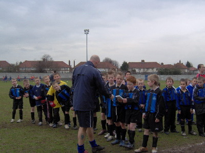 A Under 10&#039;s receives a trophy for best trainer
