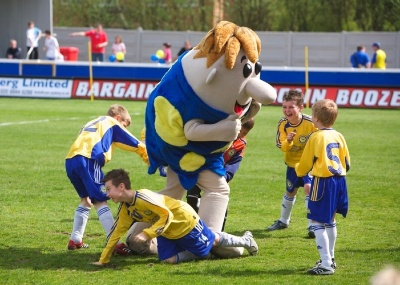 The Dragons are entertained by Farnborough mascot Farney Rubble (or is it the other way round)