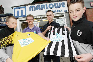 Coach Stephen Hesketh with players Caoimhin McKenna and Ciaran McAuley receiving their new kit from Gareth Burns of sponsor Marlowe Cleaners